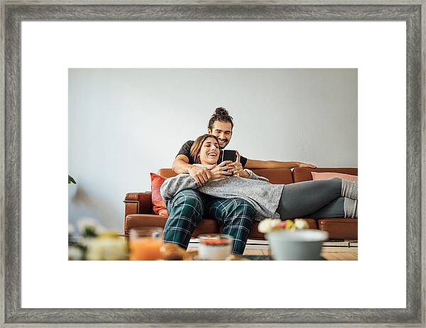 Young Couple With Smart Phone Relaxing On Sofa Framed Print by Luis Alvarez