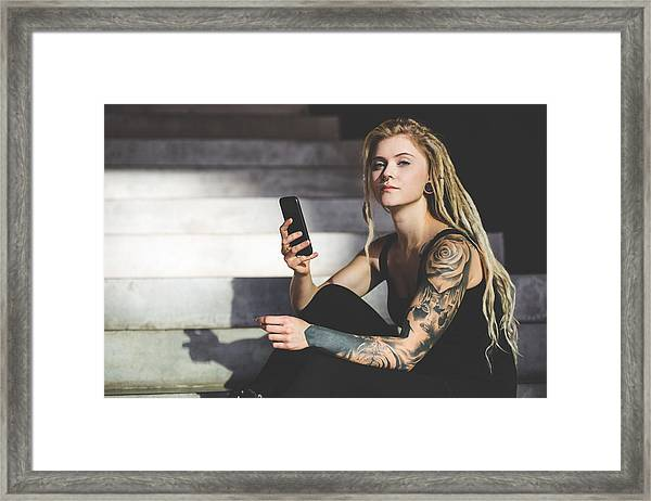 Young Tattooed Woman Texting Message On Mobile Phone Framed Print by Nikada
