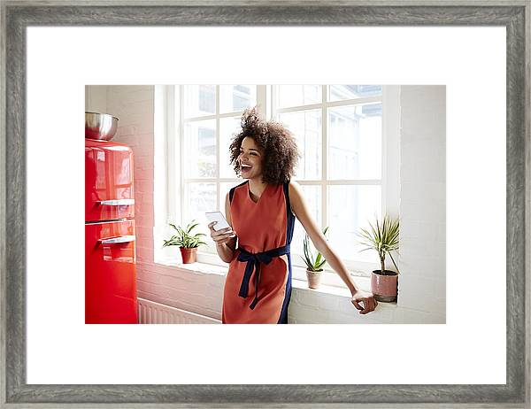 Young Woman Laughing In A Trendy Apartment Framed Print by Ezra Bailey