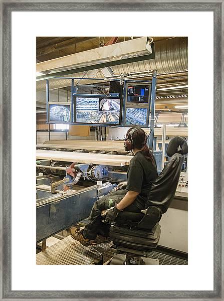 Young Woman Using Control Panel While Monitoring Computer Screens At Sawmill Framed Print by Hakan Jansson