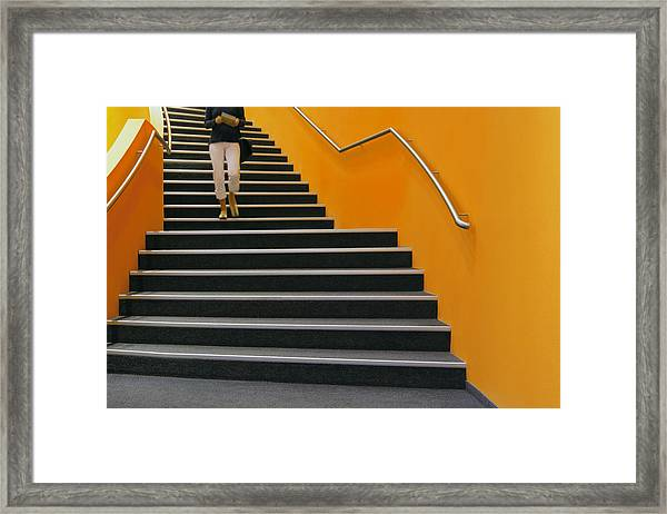 Young Woman Walking Down Orange Stairs, Reading Book Framed Print by B&M Noskowski
