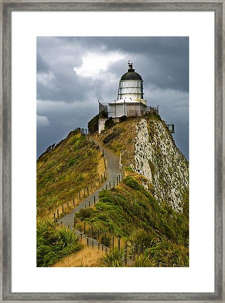 Nugget Point Light House And Dark Clouds In The Sky Framed Print