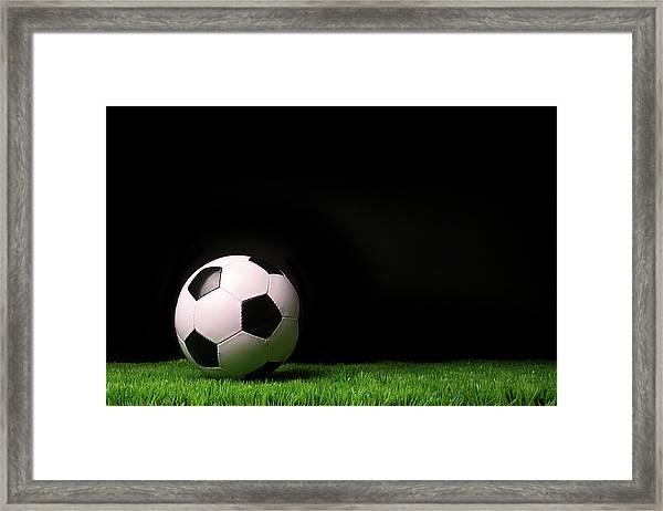 Soccer Ball On Grass Against Black Framed Print