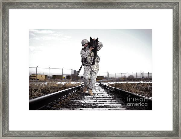 A Military Dog Handler Uses An Framed Print