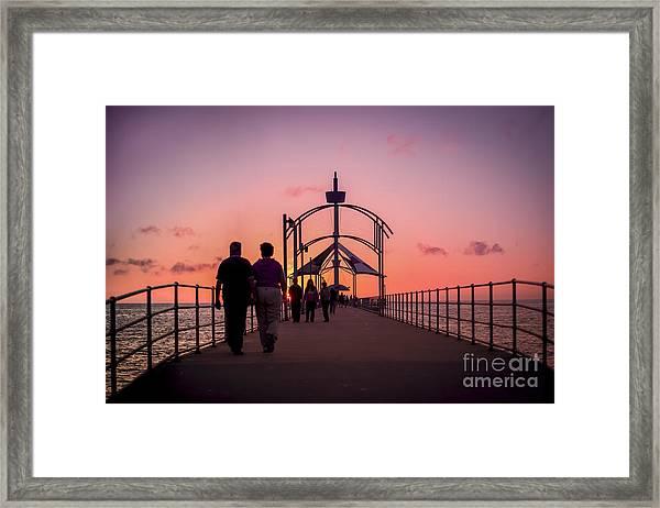 A Stroll Along Sunset Pier Framed Print