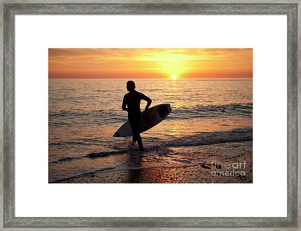 A Young Man Surfing At Sunset Off Aberystwyth Beach, Wales Uk Framed Print