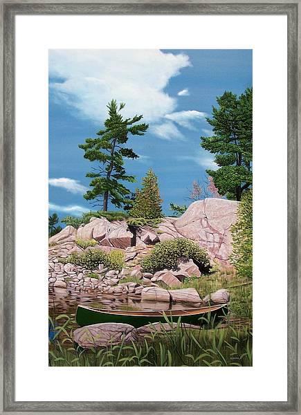 Canoe Among The Rocks Framed Print