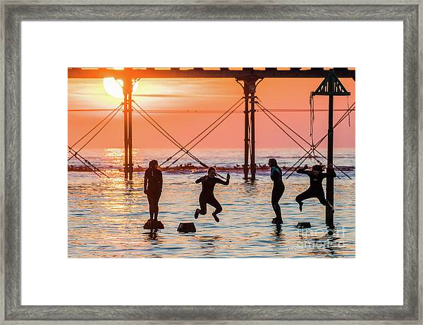 Four Girls Jumping Into The Sea At Sunset Framed Print