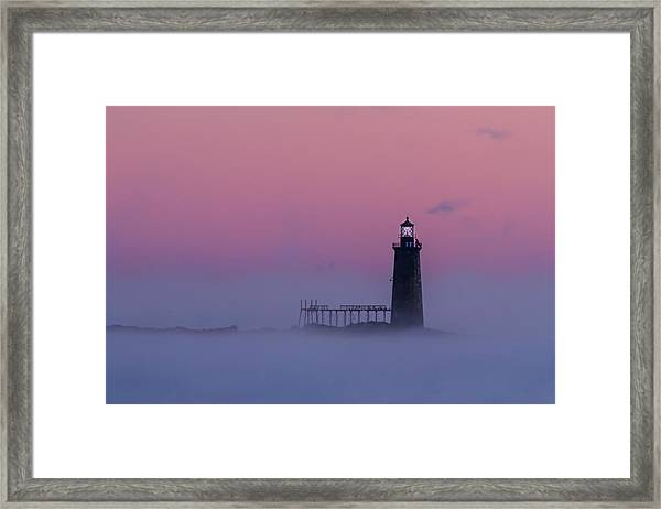 Lighthouse In The Clouds Framed Print