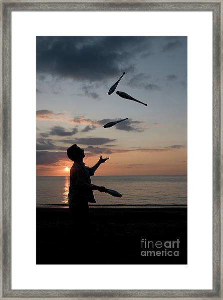 Man Juggling With Four Clubs At Sunset Framed Print
