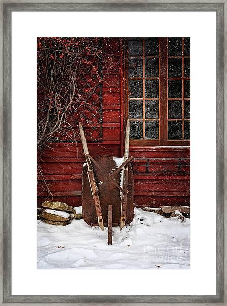 Rusty Wheelbarrow Leaning Against Barn In Winter Framed Print
