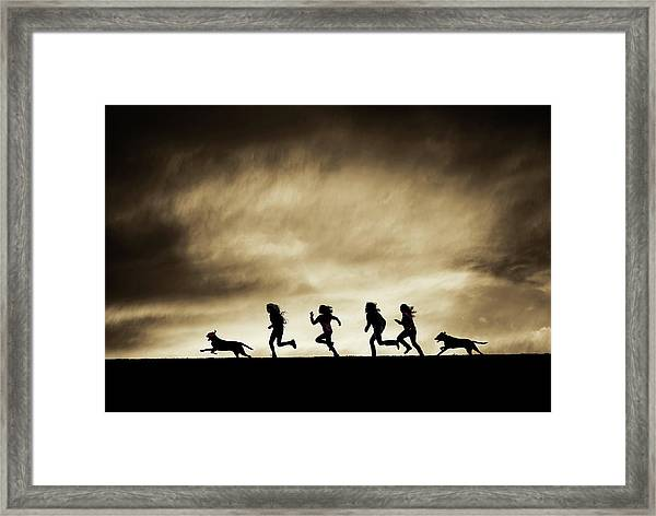 Silhouettes Of Running Girls And Dogs  Framed Print