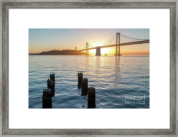 Six Pillars Sticking Out The Water With Bay Bridge In The Backgr Framed Print