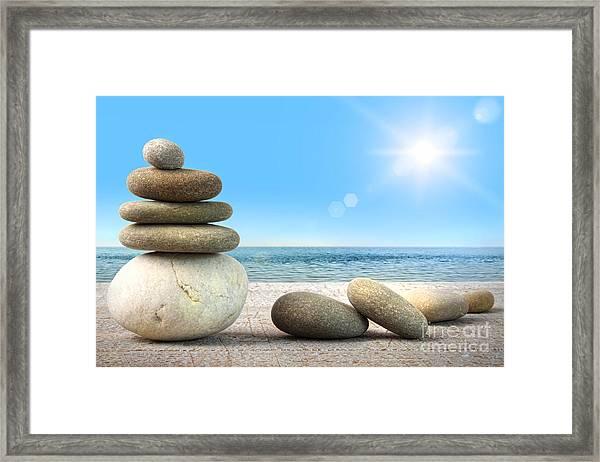 Stack Of Spa Rocks On Wood Against Blue Sky Framed Print