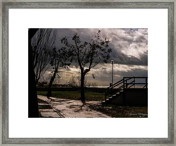 Strolling The Waterfront On A Stormy Day Framed Print