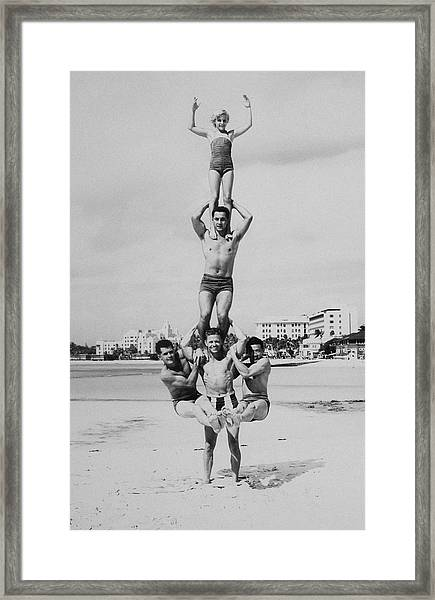Men And Girl Perform Acrobatics On Beach Framed Print