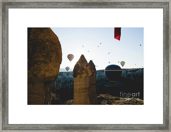 hot air balloons for tourists flying over rock formations at sunrise in the valley of Cappadocia. Framed Print