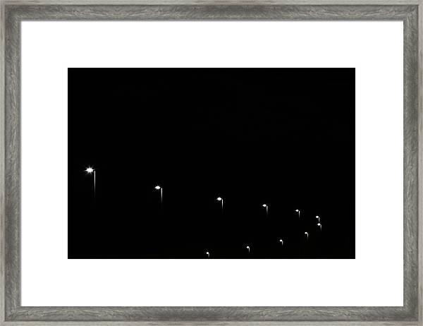 A Curved Line Of Street Lights Framed Print