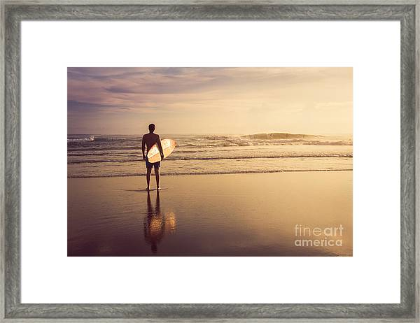 A Man Is Standing With A Surf In His Framed Print