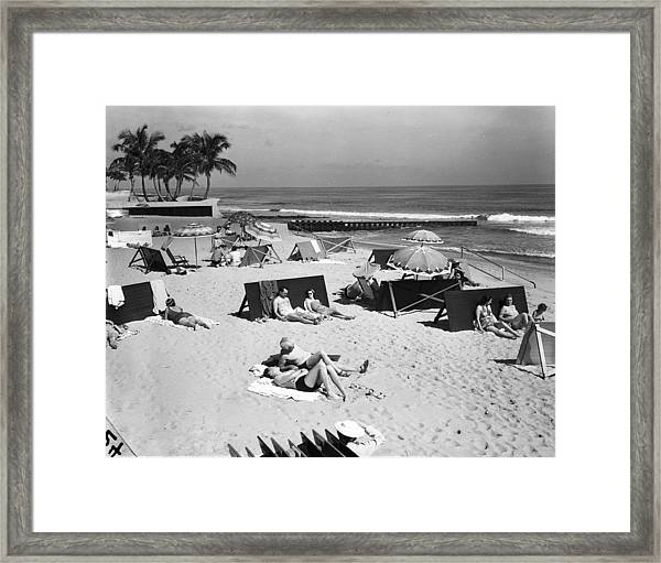 A View Of Sunbathers Lying On A Beach Framed Print