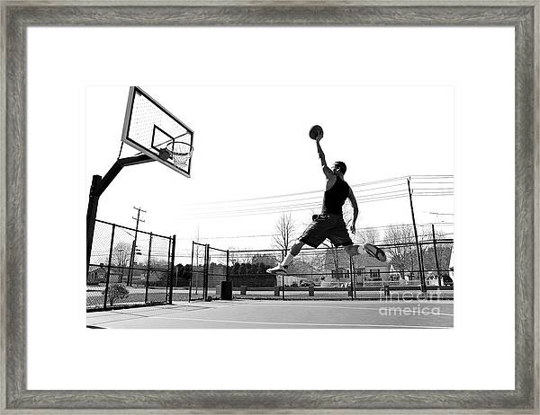 A Young Basketball Player Flying Framed Print