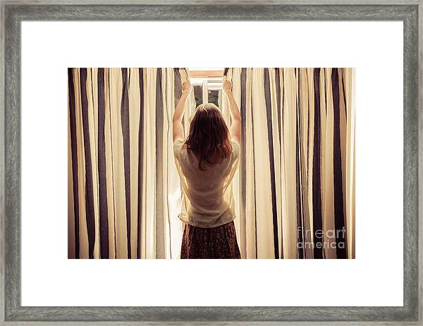 A Young Woman Is Opening The Curtains Framed Print