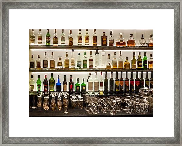 Backlit Bottles And Glassware Behind A Framed Print