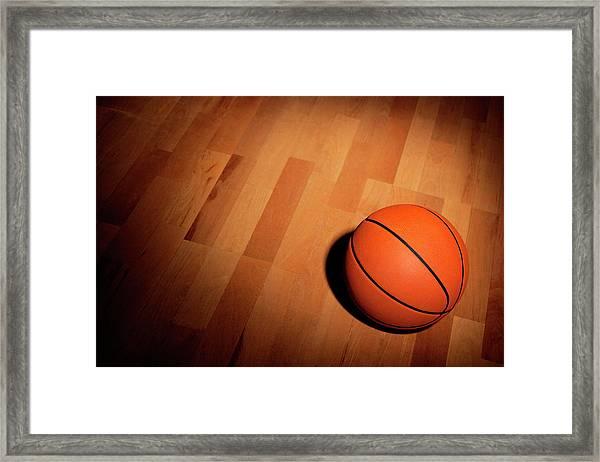 Basketball On A Wood Court Framed Print