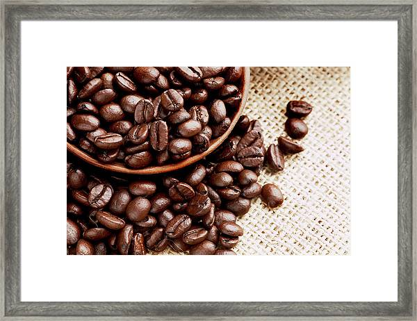 Coffee Beans Spilling From Wooden Bowl Framed Print by Joseph Clark