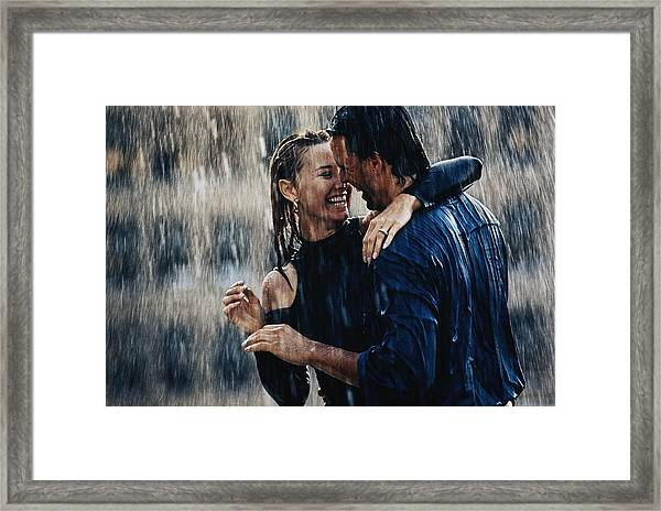 Couple Embracing In Pouring Rain Framed Print by Bruce Ayres