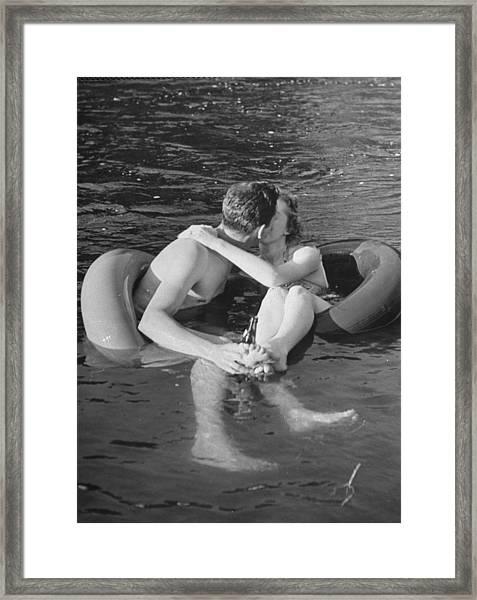 Couple Kissing While Innertube Floating Framed Print