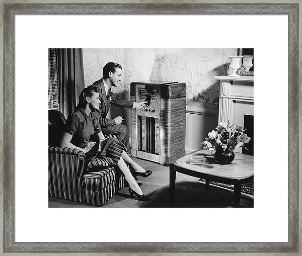 Couple Listening To Radio In Living Framed Print