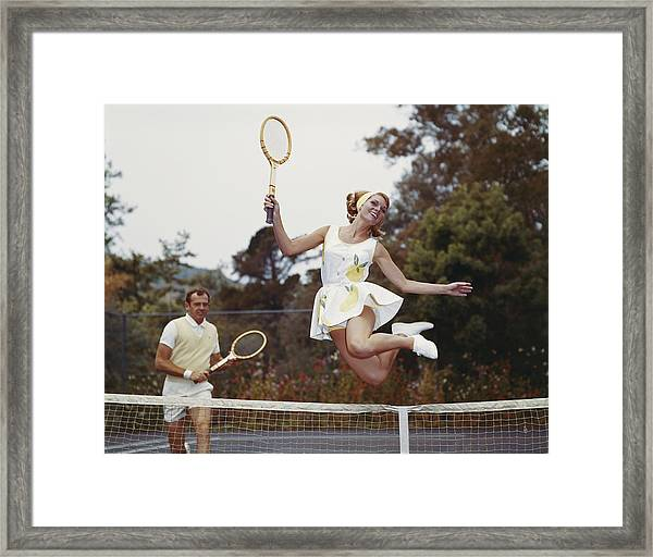Couple On Tennis Court, Woman Jumping Framed Print