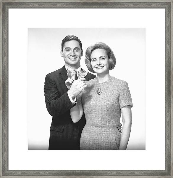 Couple Toasting Champagne In Studio Framed Print