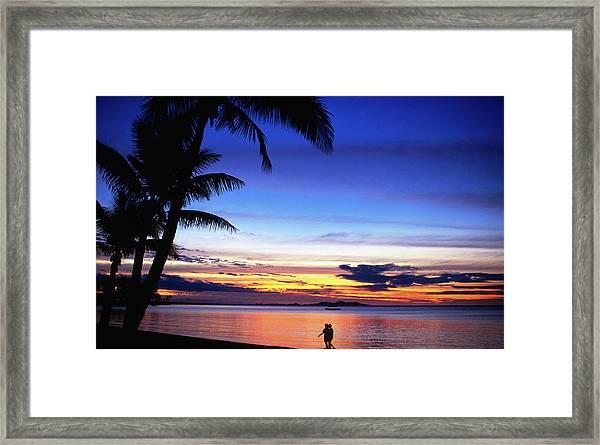 Couple Walking Along Beach At Sunset Framed Print