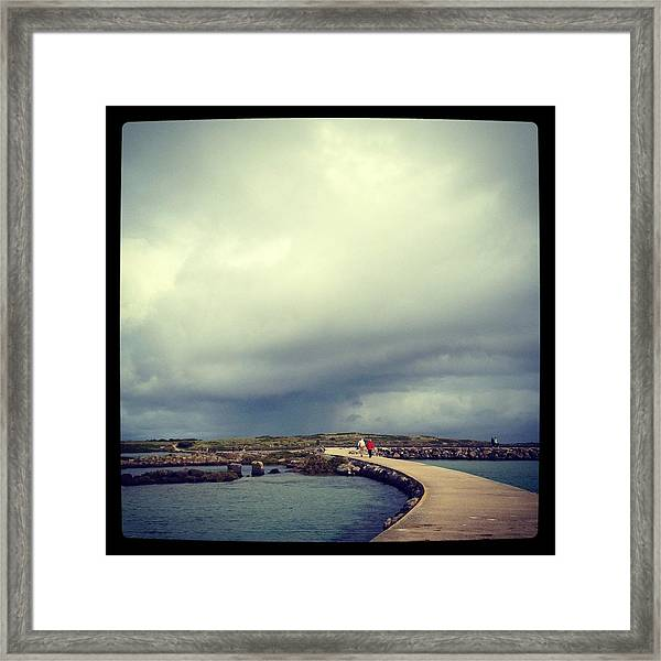 Couple Walking Along Pathway To Island Framed Print