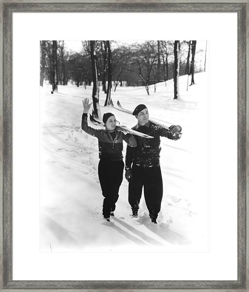 Couple Walking In Snow Skiing Framed Print