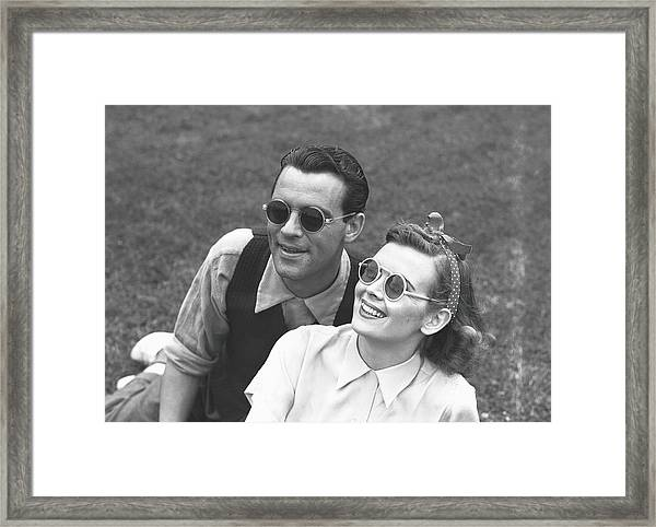 Couple Wearing Sunglasses Sitting On Framed Print by George Marks