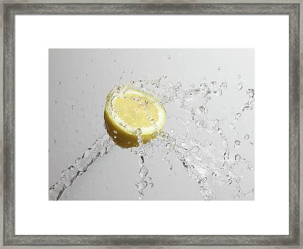 Cut Lemon Splashed With Water Framed Print