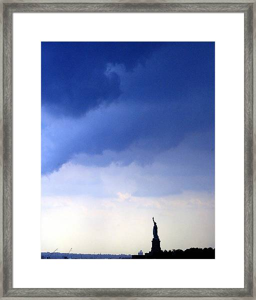 Dark Clouds Roll Towards The Statue Of Framed Print