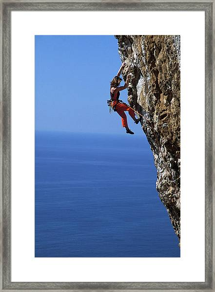 Female Free Climber Scaling Rock Face Framed Print