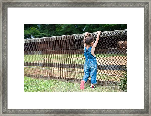 Girl Playing Wearing Overalls Framed Print