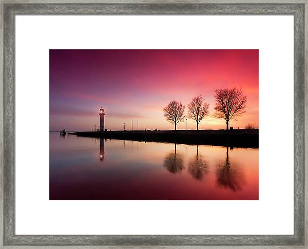 Harbor Jetty And Lighthouse At Sunset Framed Print