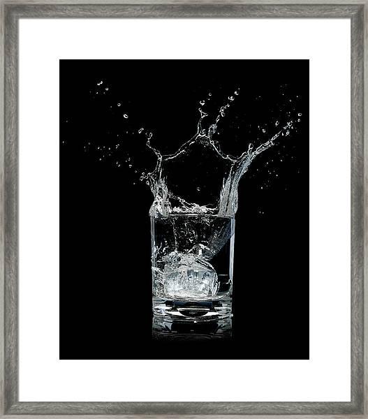 Ice Splashing Into Water Glass Framed Print by Chris Stein