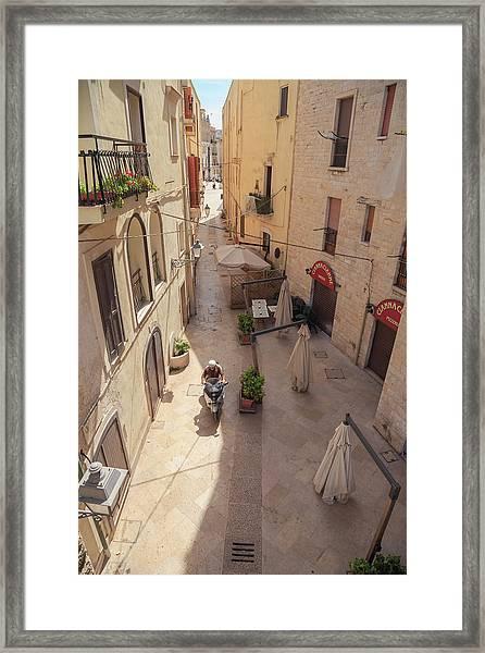 Man Rides Scooter Through Bari Framed Print