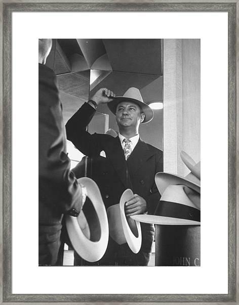 Man Trying On Hats At Nieman Marcus Depa Framed Print by Nina Leen