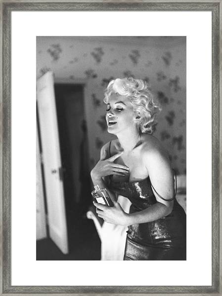 Marilyn Monroe With Chanel No. 5 Framed Print by Michael Ochs Archives