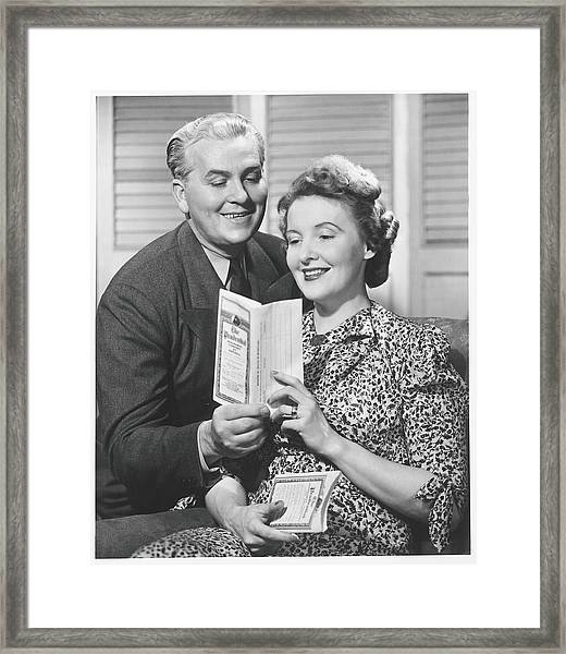 Mature Couple Looking At Brochure, B&w Framed Print by George Marks