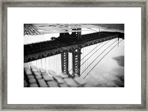 Reflection Of Bridge In Puddle Framed Print