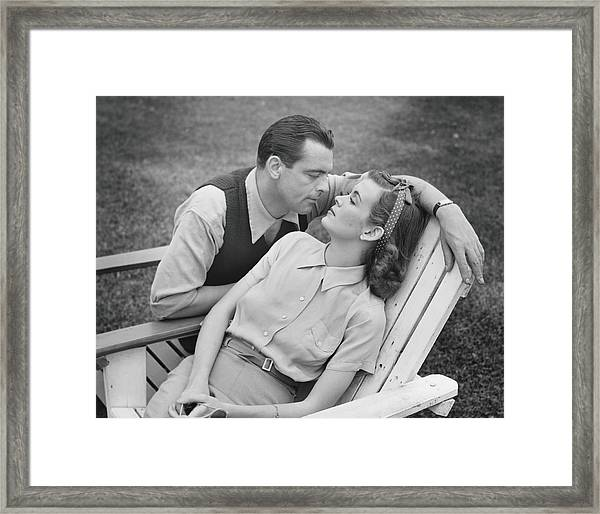 Romantic Couple Relaxing On Deckchair Framed Print by George Marks
